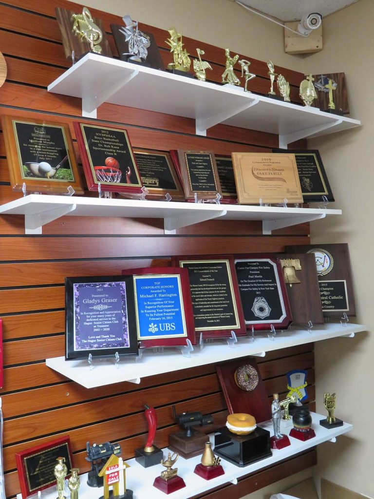 plaques and trophies on shelves on wall