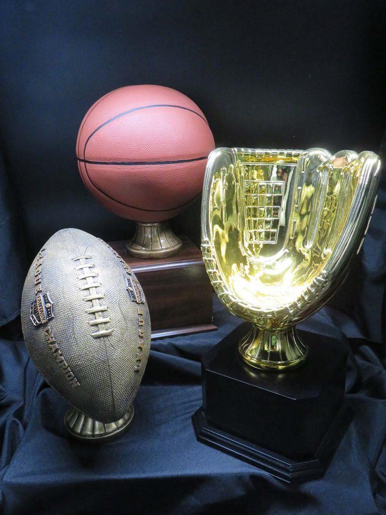 baseball glove, football and basketball trophies